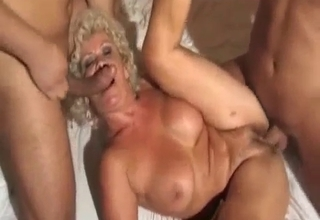 Leathery blonde MILF takes two cocks