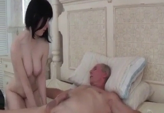Pale-skinned brunette riding on a bed